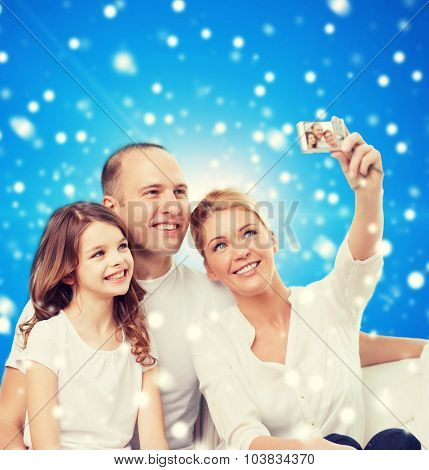 family, holidays, christmas, technology and people - smiling family  making selfie with camera over blue snowy background