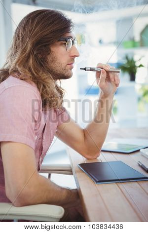 Side view of hipster smoking electronic cigarette at desk in office