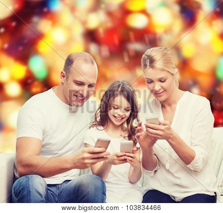 family, holidays, technology and people concept - smiling mother, father and little girl with smartphones over red lights background