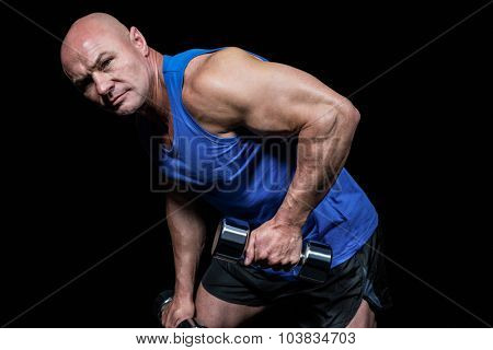Portrait of fit man exercising with dumbbells against black background