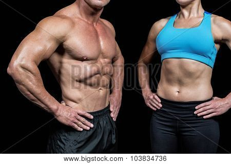 Midsection of muscular man and woman with hands on hip against black background