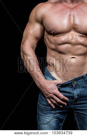 Midsection of sexy man pulling denim while standing against black backrgound