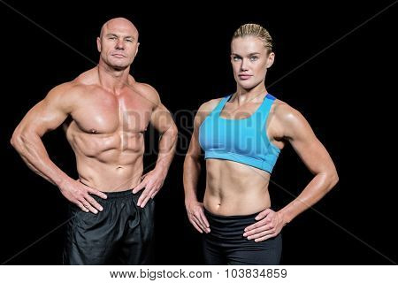 Portrait of confident man and woman with hands on hip standing against black background