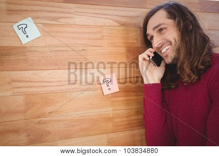 Happy man using mobile phone leaning on wooden wall in office