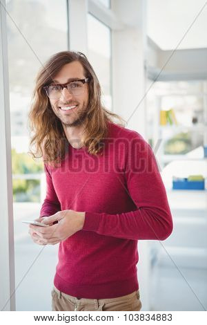 Portrait of happy hipster using mobile phone while standing by window in office