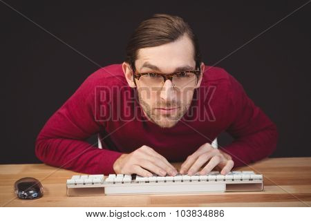 Portrait of concentrated man working on computer at desk in office