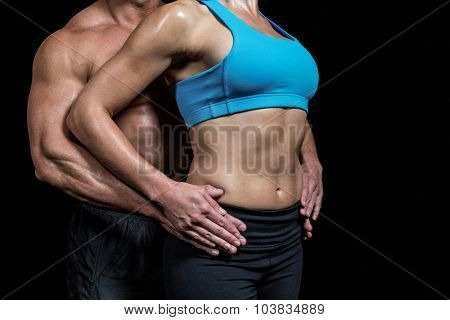 Midsection of healthy couple with hands on hip against black background