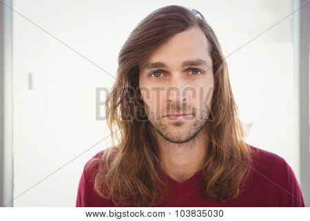 Portrait of confident hipster against window in office