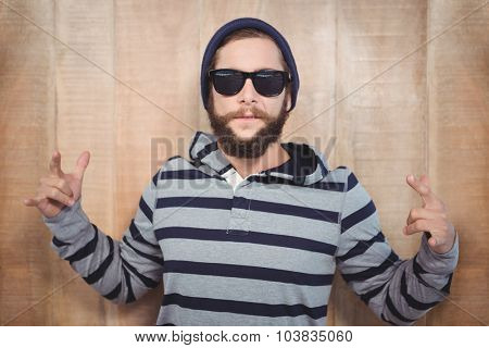 Hipster showing rock and roll hand sign against wooden wall