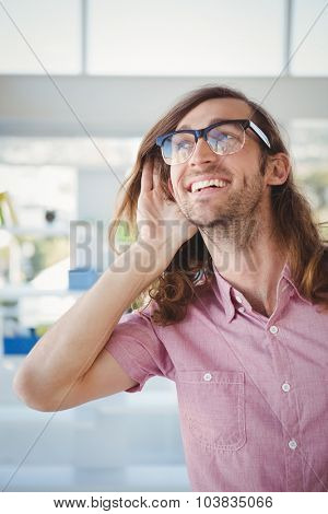 Happy hipster cupping hands to ear while standing in office