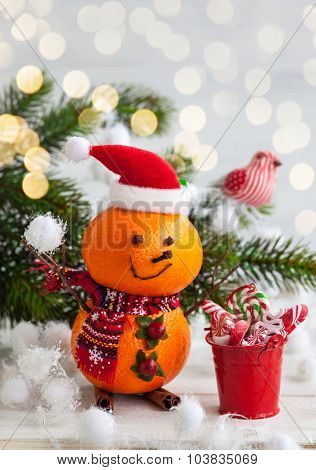 Happy snowman made out of tangerines,clove and winter berries