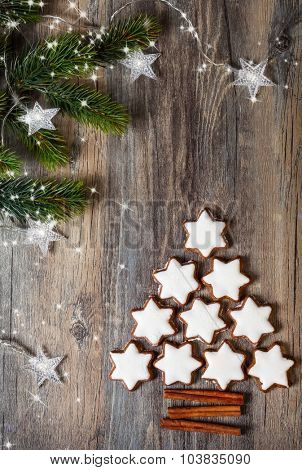 Christmas background with gingerbread cookies,fir branches,christmas lights and spices on the old wooden board
