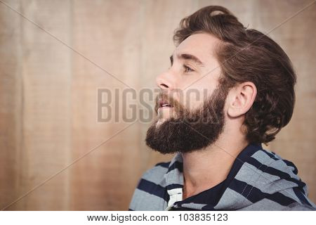 Close-up of thoughtful hipster looking away against wooden wall