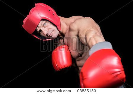 Portrait of boxer with gloves and headgear punching against black background