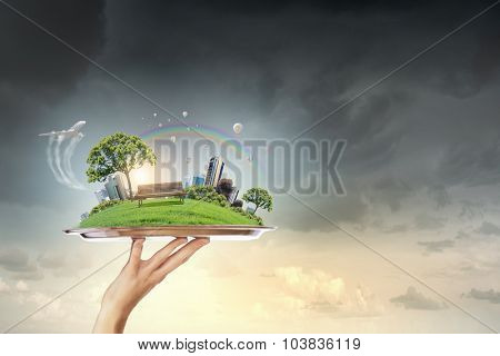 Hand holding metal tray with modern cityscape