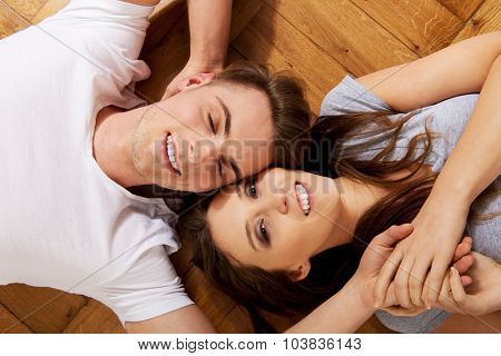 Young happy couple lying on the floor.