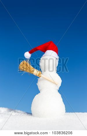 Snowman With A Pointed Cap And A Broom In The Snow