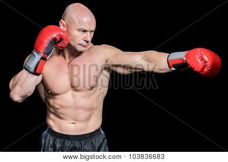Bald boxer in fighting stance against black background