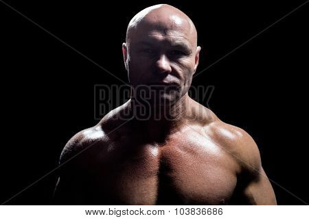 Portrait of on muscular man against black background