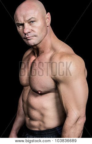 Portrait of shirtless muscular man against black background