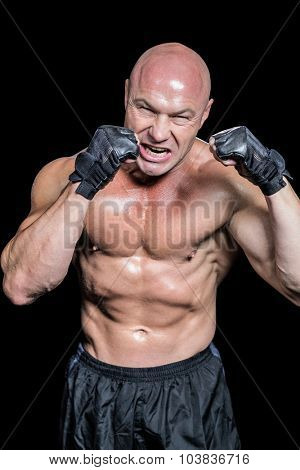 Angry bald fighter with gloves against black background