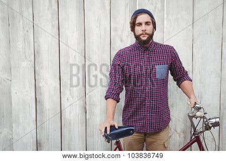 Hipster with bicycle standing against wooden fence