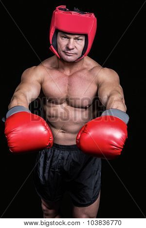 Portrait of boxer with red gloves and headgear against black background