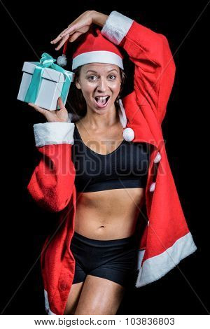 Portrait of cheerful athlete holding Christmas gift while standing against black background