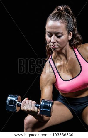 Serious fit woman lifting dumbbell sitting against black background