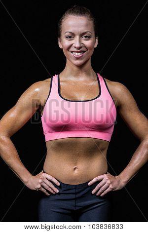 Portrait of happy slim woman against black background