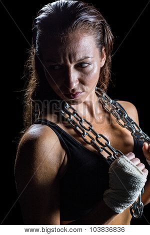 Annoyed female athlete holding chain against black background