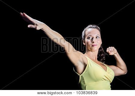 Beautiful confident athlete stretching hands against black background