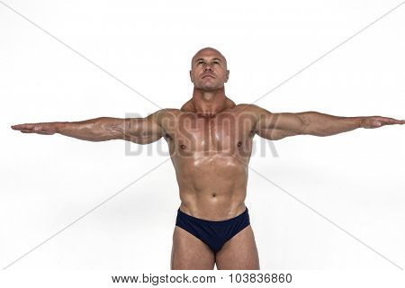 Muscular man with arms outstretched against white background