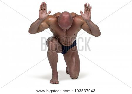 Muscular man bending on knee with arms raised against white background