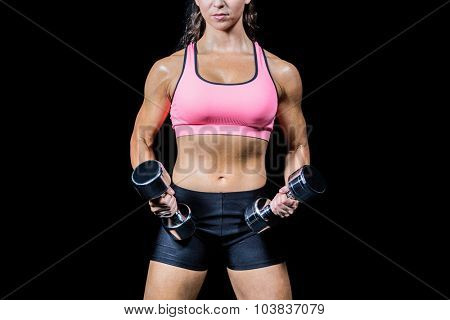 Midsection of woman exercising with dumbbells against black background