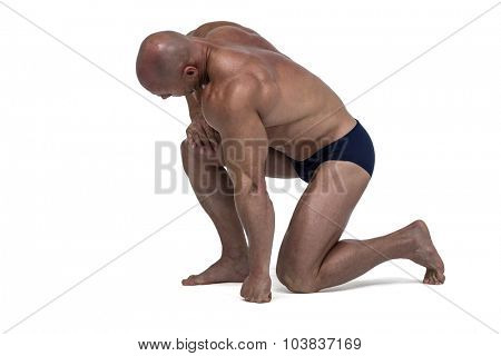 Athlete exercising while kneeling down against white background