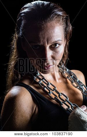 Portrait of female fighter holding chain against black background