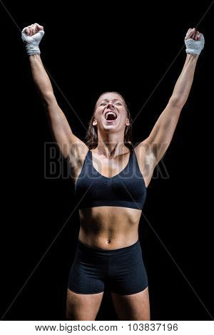 Cheerful winning athlete with arms raised against black background