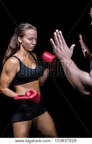 Female boxer hitting on trainer hand against black background