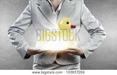 Businesswoman holding in hands yellow toy rubber or plastic duck