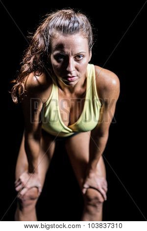 Portrait of exhausted athlete bending against black background
