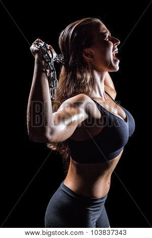 Side view of angry athlete shouting while holding chain against black background