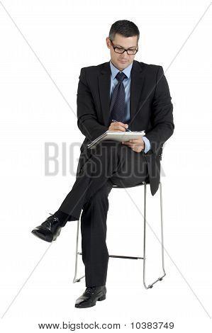 sitting businessman with eyeglasses writing isolated on white background