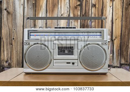 Vintage boombox on wood table with rustic cabin wood wall.