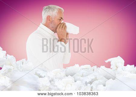 Sick man in winter fashion sneezing against pink vignette
