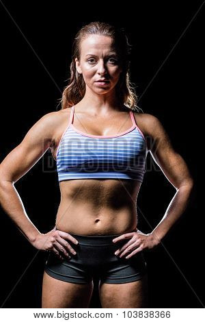 Portrait of female athlete with hands on hip against black background