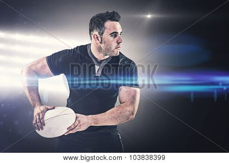 Rugby player throwing the ball against spotlight