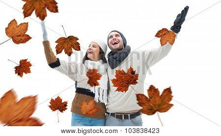 Young winter couple against autumn leaves pattern