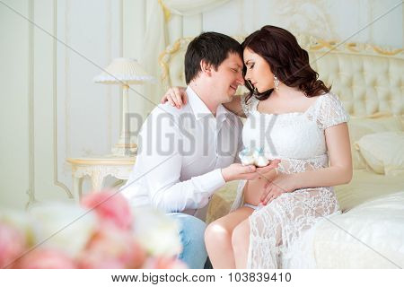 Happy Family. Young Pregnant Couple With Baby Booties For Newborn Boy
