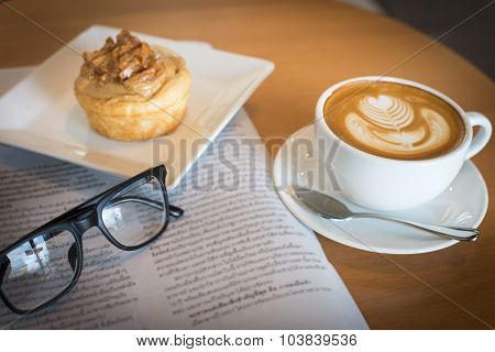 Apple Cinnamon Roll Served With Latte Art Coffee And Newspaper On The Table At Restaurant